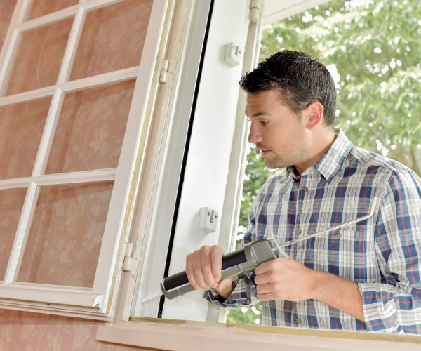 man caulking up window